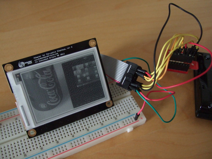 "An e-paper display connected to the Ben NanoNote via a cable and the Sparkfun ""microSD Sniffer"" board"
