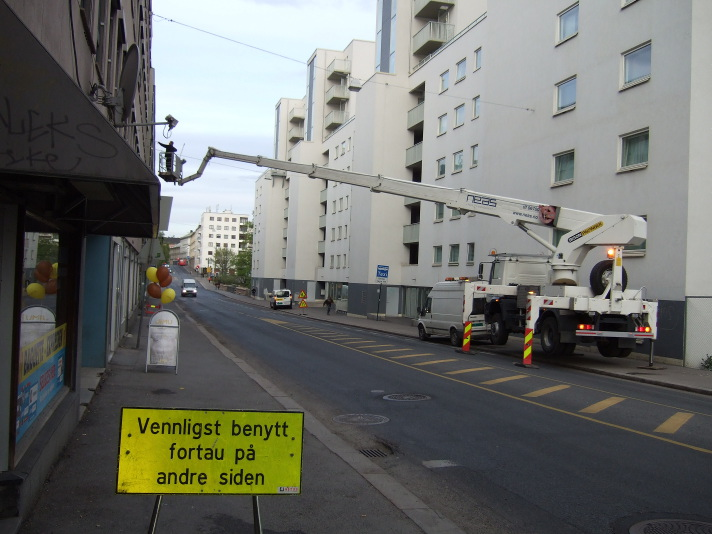 "Inconvenience: a crane operating over one pavement while sitting on the other, with a sign reading ""please use the pavement on the other side"""